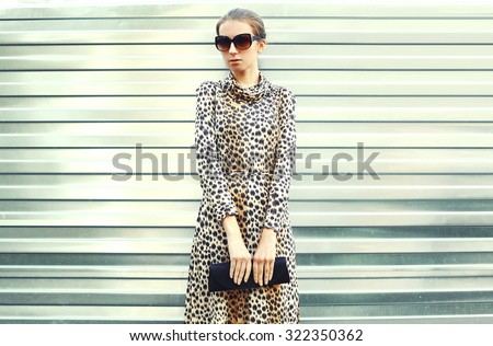 Fashion pretty young woman in sunglasses and leopard dress with handbag clutch over metal background - stock photo