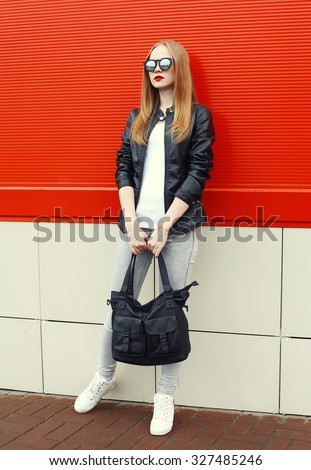 Fashion pretty young woman wearing a rock black leather jacket, sunglasses and bag over red background - stock photo