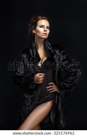 Fashion seductive brown hair lady in an elegant fur coat and black underwear on a dark background  - stock photo