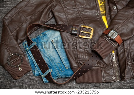 Fashion set: leather jacket, jeans with a belt, shirt, watch and bracelet on the arm - stock photo