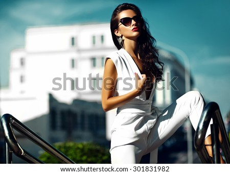 Fashion sexy hot businesswoman girl model in white suit in sunglasses in the street - stock photo