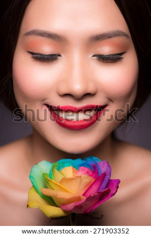 Fashion Sexy Woman with flowers. Vogue style Model girl face with roses. Red Sexy Lips closeup. Manicure and Makeup. Make up. Beauty lady face isolated on black background. Perfect skin. - stock photo