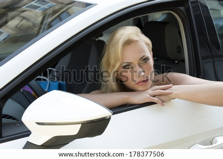 fashion shoot of cute blonde woman sitting in a white car with colorful shopping bag near and sensual eyes  - stock photo