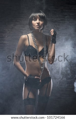 Fashion shoot of young bizarre woman in fetish dress