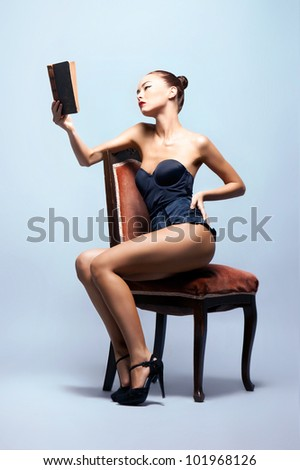Fashion shoot of young sexy woman reading books in nice lingerie - stock photo