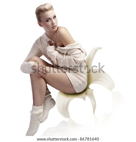 fashion shot of a beautiful blonde with an up-do wearing a warm white woolen sweater and socks