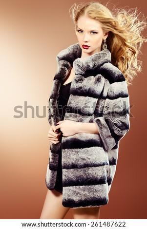 Fashion shot of a beautiful blonde woman wearing jewelry and fur coat. Studio shot. - stock photo