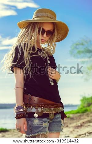 Fashion shot of a beautiful boho style girl over sky background. Boho, hippie. - stock photo