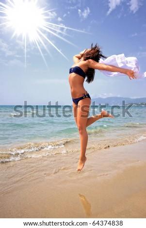 Fashion shot of a beautiful woman in a bikini on the beach - stock photo