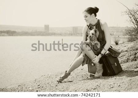 Fashion shot of a beautiful woman sitting on suitcase on the banks of the lake with the dog (Yorkshire terrier). In Black & White - stock photo