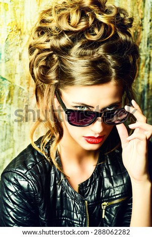 Fashion shot of a gorgeous young woman wearing black leather jacket and sunglasses.