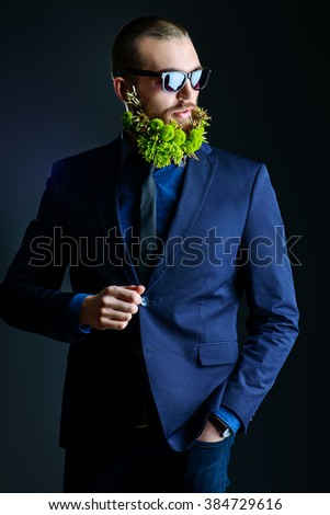 Fashion shot of a handsome man with a beard of green flowers. Men's beauty. Barbershop. - stock photo