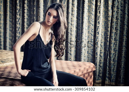 Fashion shot of a stunning brunette beauty in a room with classic vintage interior.  - stock photo