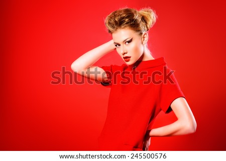 Fashion shot of a stunning female model in red dress posing at studio over red background. Beauty, fashion. - stock photo