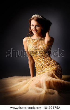 Fashion shot of a stunning woman in luxurious golden dress. Over dark background. - stock photo