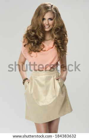 Fashion shot of a woman in gold skirt  - stock photo