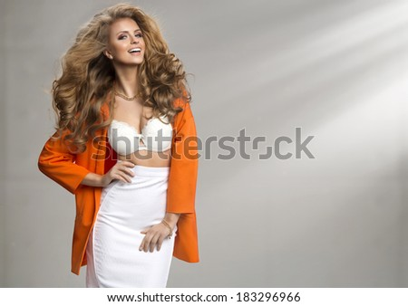Fashion shot of a woman in orange coat  - stock photo