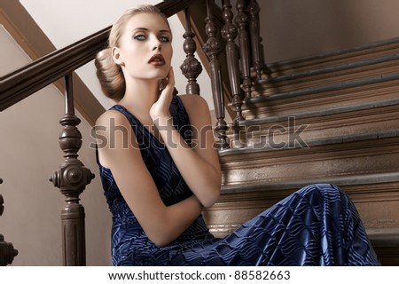 fashion shot of a young and pretty girl in blue long elegant dress sitting on a old fashion stairwell - stock photo