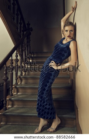 fashion shot of a young and pretty girl in blue long elegant dress standing on the stair of an old building - stock photo