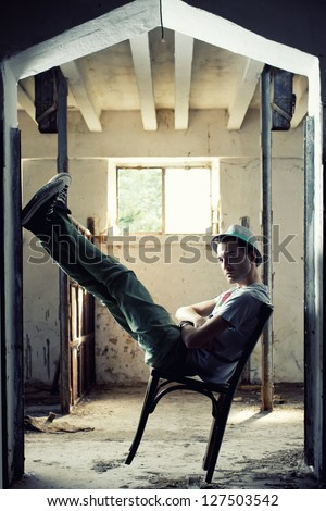 fashion shot of a young elegant man sitting chair - stock photo