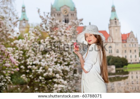 fashion shot of a young woman against Neus Rathaus Hannover, The New Town City Hall - stock photo