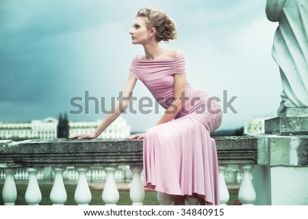 fashion shot of a young woman sitting near the sculpture in old mansion - stock photo
