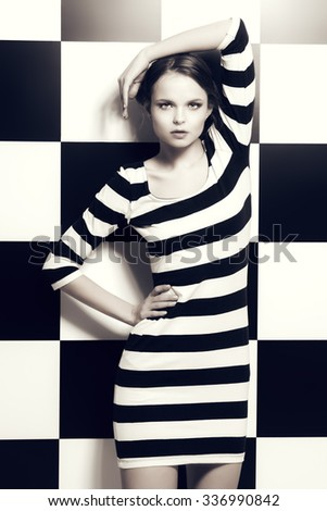 Fashion shot of an elegant model posing in dress in black and white stripes on a background of black and white squares. Beauty, fashion concept. Black-and-white photo. - stock photo