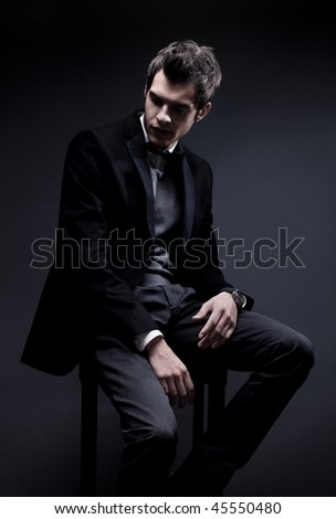 fashion shot of an elegant young man wearing suit and bow tie - stock photo