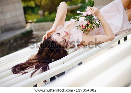 Fashion shot of beautiful girl in stylish dress with a bouquet of flowers in his hand, lying on a park bench - stock photo