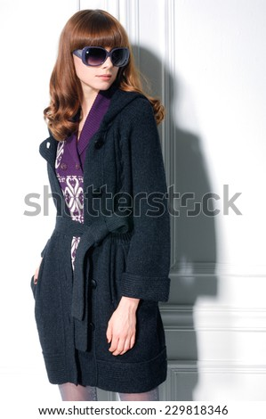 fashion shot of girl in coat with sunglasses posing  - stock photo