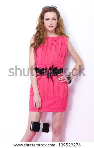 fashion shot of girl with bag posing in studio - stock photo