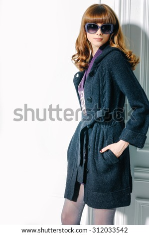 fashion shot of girl with coat in sunglasses posing in studio - stock photo