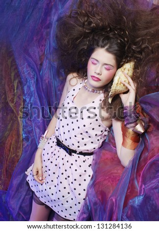 Fashion shot of woman in doll style with seashell. Creative make-up. - stock photo