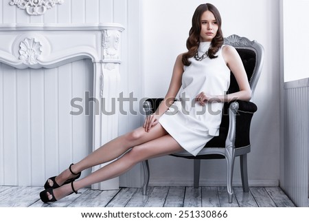 Fashion shot of young beautiful woman in white short dress sitting in antique armchair - stock photo