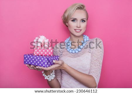 Fashion shot of young beautiful woman with pink and purple gift boxes. Studio portrait over bright pink background    - stock photo