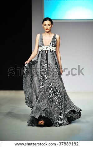 fashion show event and beautiful young woman at piste walking in luxury dress - stock photo