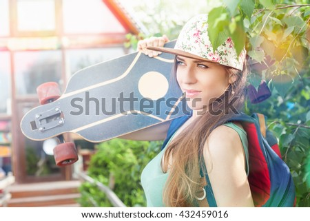 Fashion skateboarder young woman with a skateboard. Adventure, summer trip. Sport. Girl dressed in cap, wearing backpack. Accessories
