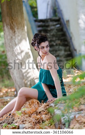 Fashion slim woman wearing green strapless short dress with gathered hair together style sitting sidewalk, beautiful scenic with dead leaves all around