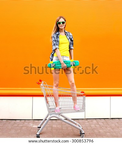Fashion smiling hipster woman having fun wearing a sunglasses and colorful clothes with skateboard standing in the shopping trolley cart over orange background - stock photo