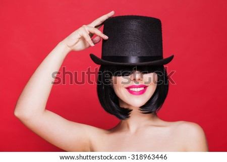 fashion smiling woman model in hat cylinder, on red background - stock photo