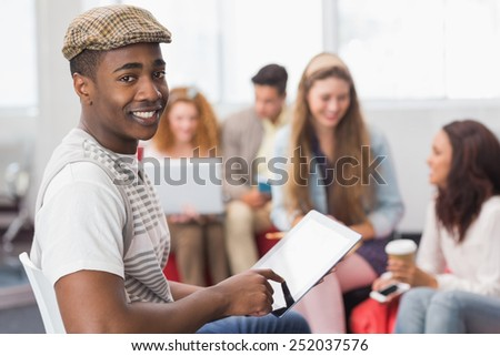 Fashion student using tablet pc at the college - stock photo