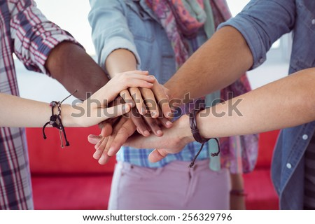 Fashion students putting hands together at the college - stock photo