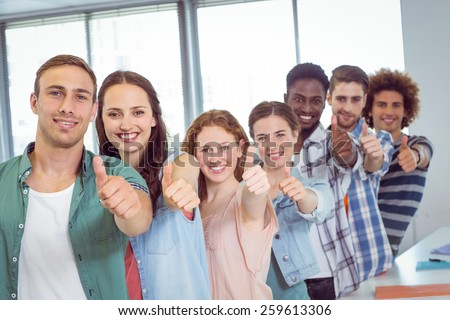 Fashion students showing thumbs up at the college - stock photo