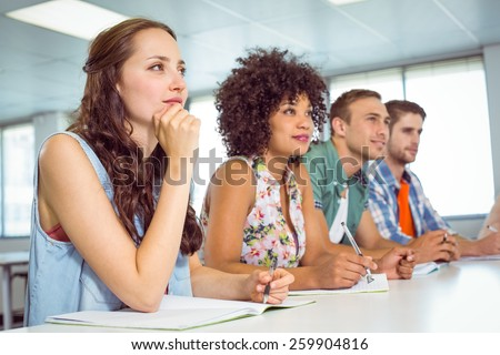 Fashion students taking notes in class at the college - stock photo