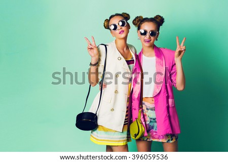 Fashion studio image of two young women in stylish casual  spring outfit   having fun, show  tongue. Bright trendy pastel  colors, stylish hairstyle  with buns , cool sunglasses. Friends portrait.  - stock photo