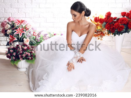 fashion studio photo of beautiful bride with dark hair in elegant wedding dress posing among bouquets of flowers