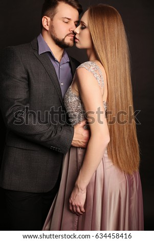 fashion studio photo of beautiful couple in elegant clothes. handsome man posing with gorgeous pregnant wife