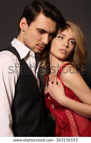 fashion studio photo of beautiful couple, wears elegant clothes, embracing each other - stock photo
