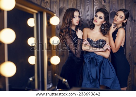 fashion studio photo of  beautiful sensual women with dark hair in luxurious dresses with bijou, posing in makeup room - stock photo