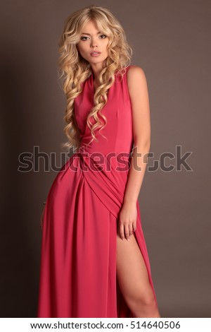 fashion studio photo of beautiful woman with blond hair in elegant red dress